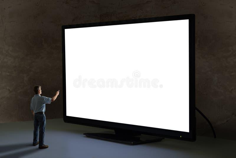 Mens die TV-afstandsbediening richten op world's grootste reuzetelevi stock fotografie