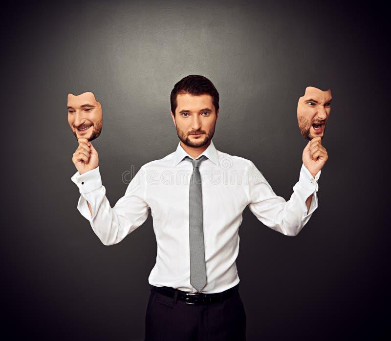 Mens die twee maskers met verschillende stemming houden stock afbeelding