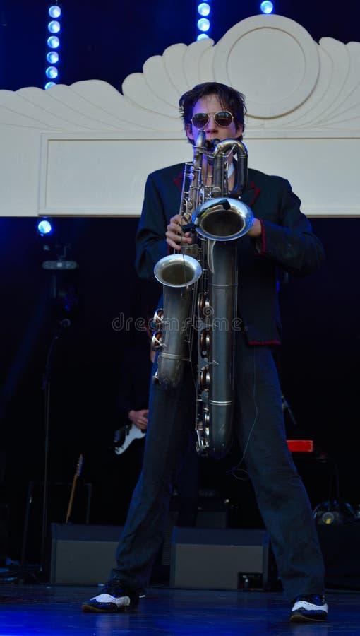 Mens die twee saxofoons tegelijkertijd spelen stock afbeeldingen