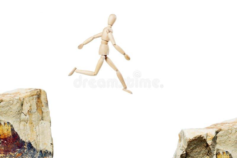 Mens die van de één rots aan een andere springen stock fotografie