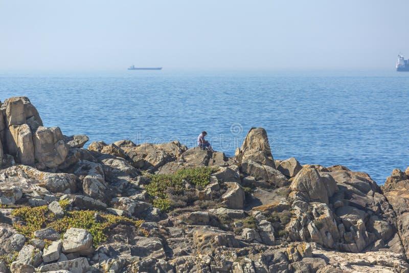 Mens die van de mening genieten, die op de rotsen, naast het strand van Leca DA Palmeira, achtergrond met oceaan en schepen zitte royalty-vrije stock afbeeldingen