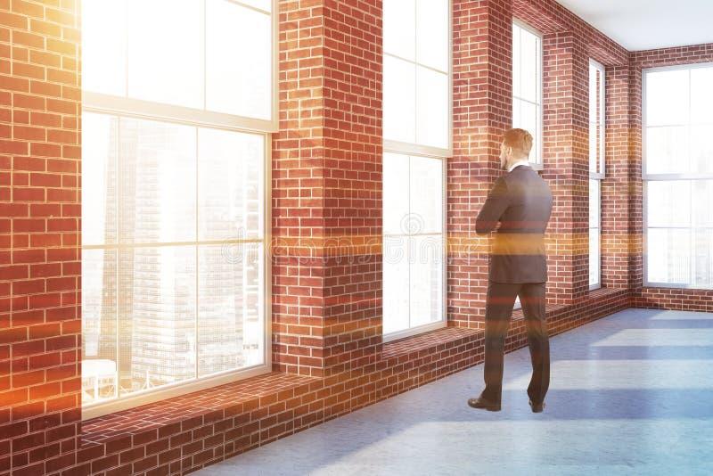 Mens die in venster van lege baksteenruimte kijken stock afbeelding