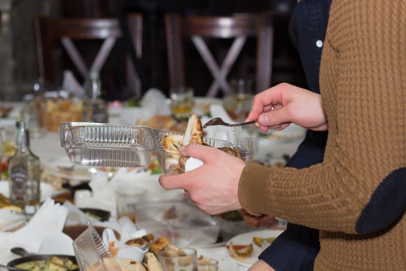 Mens die verlaten voedseldienbladen verzamelen stock fotografie
