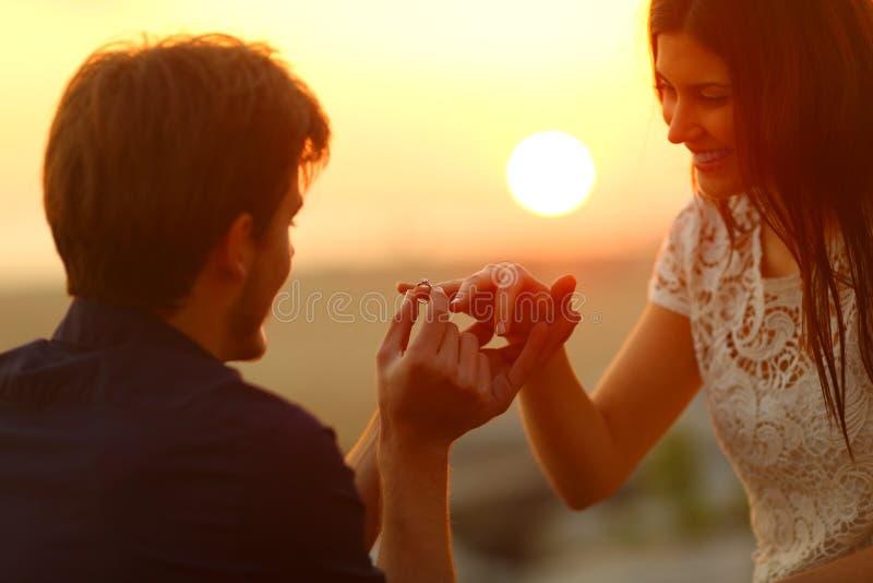 Mens die verlovingsring in meisjevinger zetten stock afbeelding