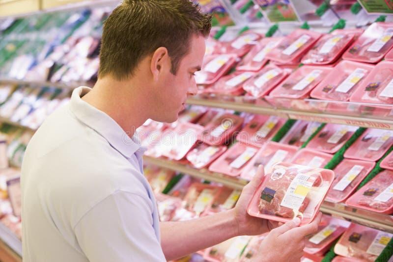 Mens die vers vlees koopt royalty-vrije stock foto's