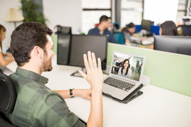 Mens die videovraag met laptop in bureau maken stock foto