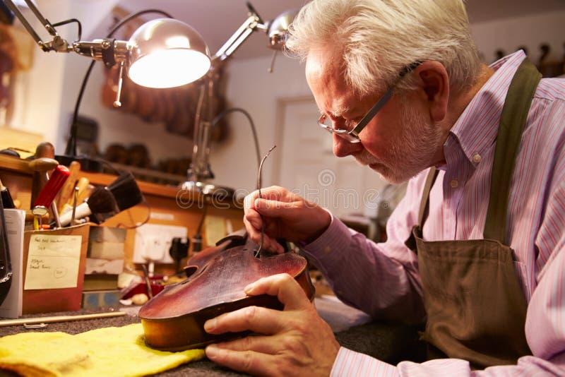 Mens die Viool in Workshop herstellen stock afbeeldingen