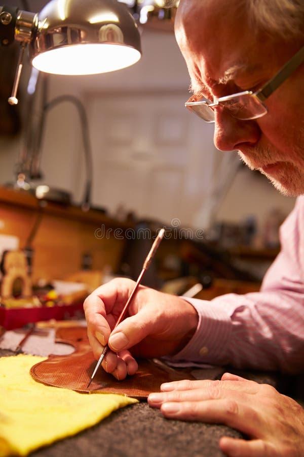 Mens die Viool in Workshop herstellen stock foto's