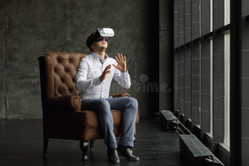 Mens die virtuele werkelijkheidsbeschermende brillen dragen die op films letten of videospelletjes spelen Het ontwerp van de vrho stock afbeeldingen