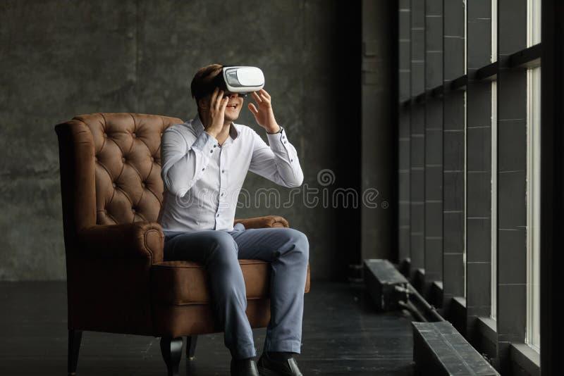 Mens die virtuele werkelijkheidsbeschermende brillen dragen die op films letten of videospelletjes spelen Het ontwerp van de vrho royalty-vrije stock fotografie