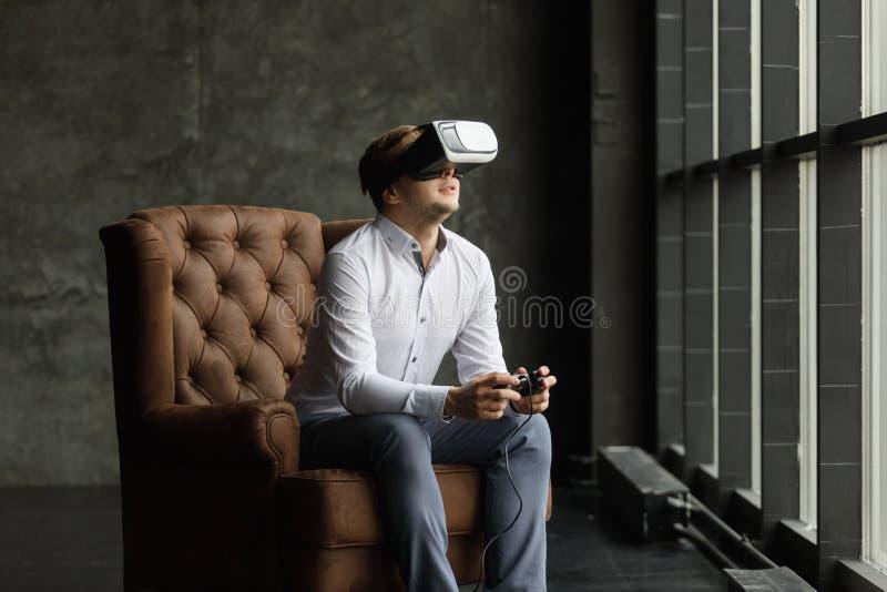Mens die virtuele werkelijkheidsbeschermende brillen dragen die op films letten of videospelletjes spelen Het ontwerp van de vrho royalty-vrije stock afbeelding