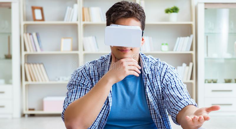 Mens die virtuele werkelijkheidsvr glazen dragen die op vloer bij ho mediteren stock afbeelding