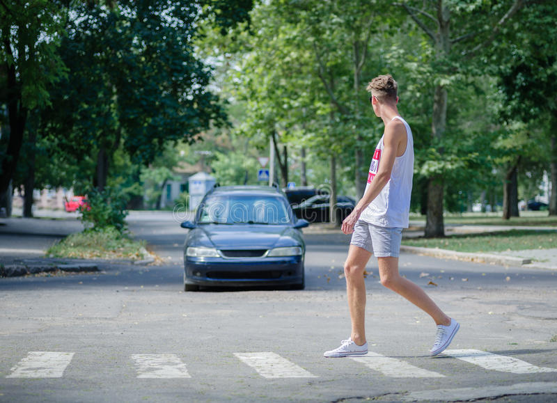 Mens die voor een auto lopen Een jongen die straat op een vage achtergrond kruisen Zorgvuldig op het wegconcept De ruimte van het stock foto's