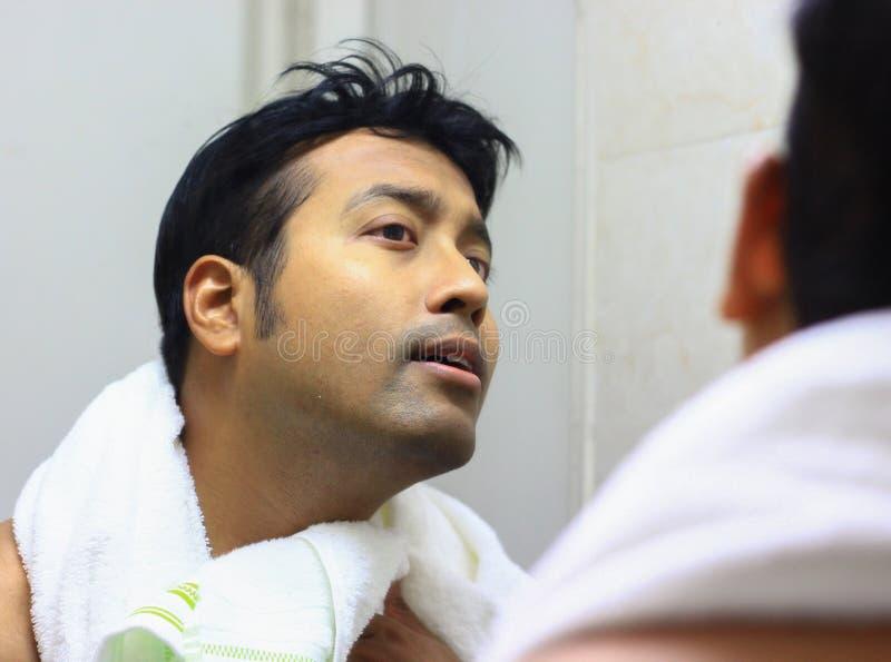 Mens die voor zijn verschijning voor een spiegelschoonheid het stileren levensstijl zorgen stock afbeeldingen