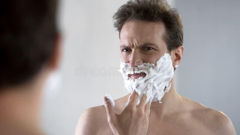 Mens die voorbereidingen treffen te scheren, voelend ongemak en tinteling op gezicht van het scheren van schuim royalty-vrije stock foto's