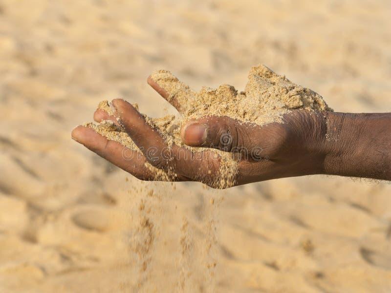Mens die wat zand in de hand houden: droogte en ontvolking stock afbeeldingen