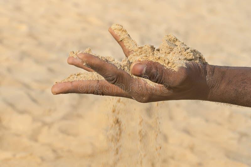 Mens die wat zand in de hand houden: droogte en ontvolking stock foto's