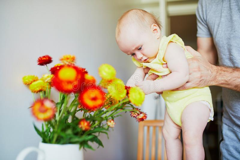 Mens die weinig babymeisje houden en haar aanrakingsbloemen laten royalty-vrije stock foto's