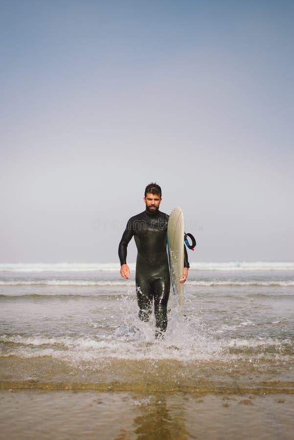 Mens die in wetsuit het water na het surfen verlaten stock fotografie