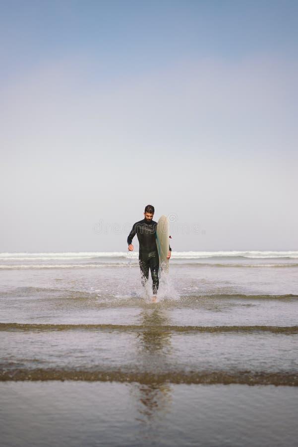 Mens die in wetsuit het water na het surfen verlaten royalty-vrije stock foto's