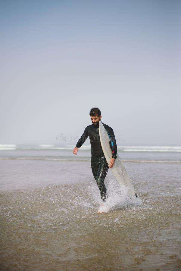 Mens die in wetsuit het water na het surfen verlaten stock afbeelding
