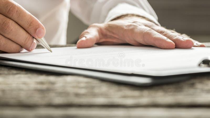 Mens die in wit overhemd bedrijfsdocument ondertekenen royalty-vrije stock fotografie