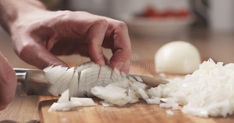 Mens die witte ui met mes snijden stock afbeeldingen