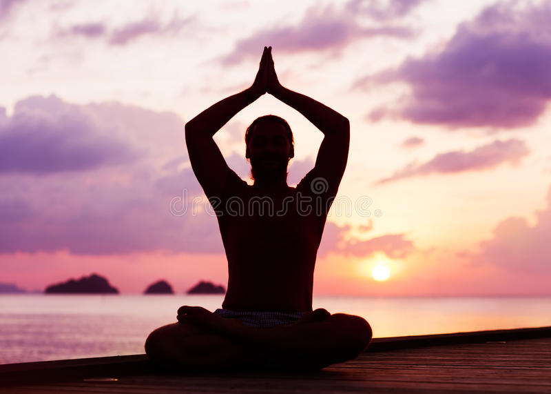 Mens die yoga doen bij Zonsondergang stock fotografie