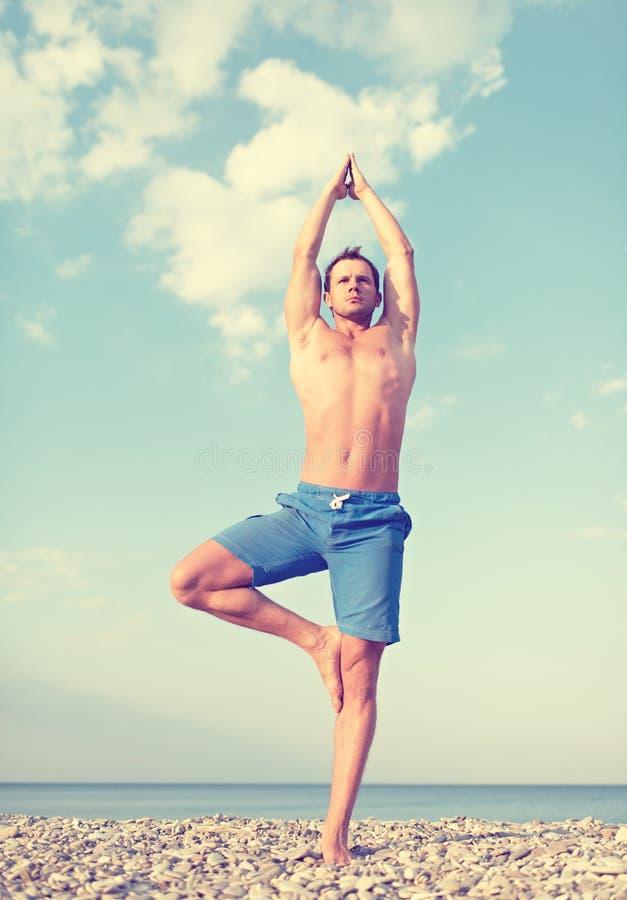Mens die yoga op het strand doen royalty-vrije stock foto