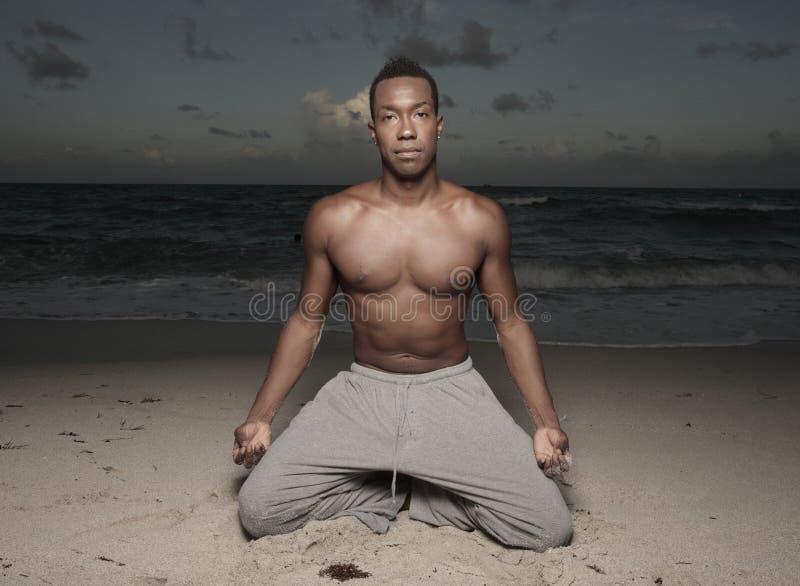 Mens die yoga op het strand uitvoert royalty-vrije stock fotografie