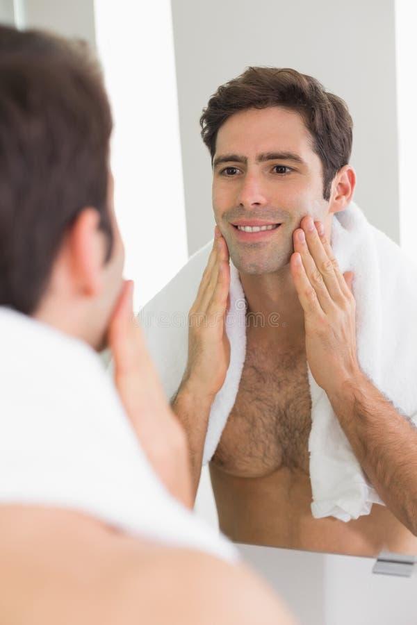 Mens die zelf in spiegel in de badkamers bekijkt stock afbeeldingen