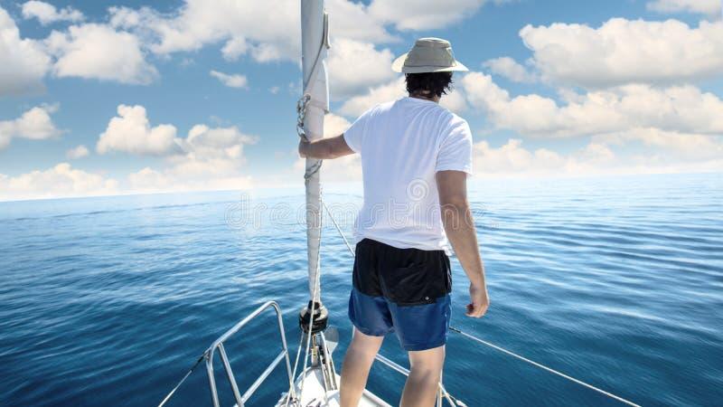 Mens die zich bij de boog van een schip bevinden Zeilen, vakantie en vrijheidsconcept royalty-vrije stock afbeeldingen