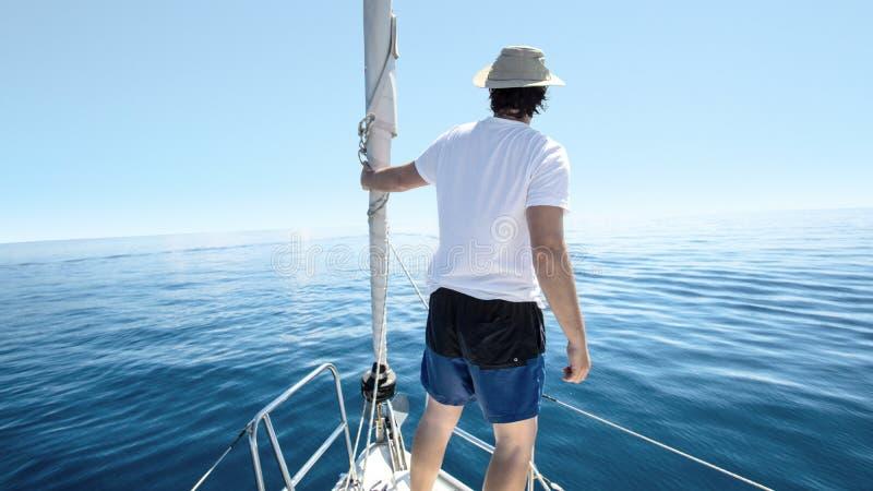 Mens die zich bij de boog van een schip bevinden Zeilen, vakantie en vrijheidsconcept stock afbeeldingen