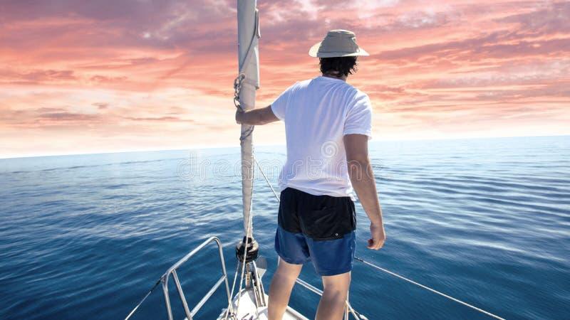 Mens die zich bij de boog van een schip bevinden Zeilen, vakantie en vrijheidsconcept stock foto's