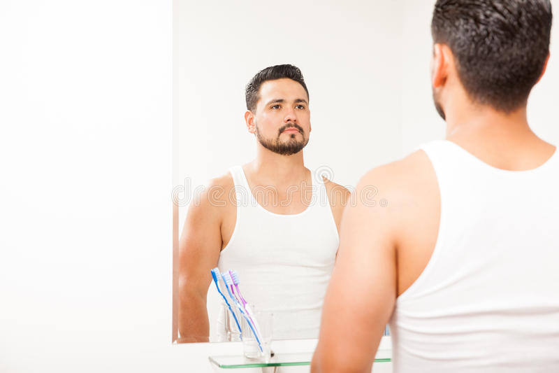 Mens die zich in de badkamersspiegel bekijken royalty-vrije stock afbeeldingen