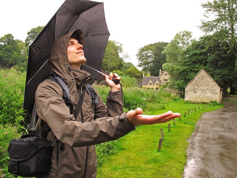 Mens die zich in de regen bevinden stock afbeeldingen