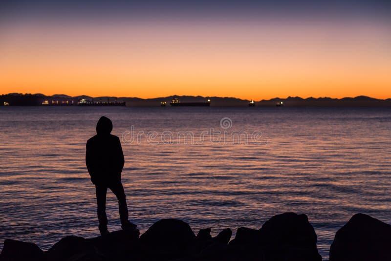 Mens die zich door de oceaan bevinden die uit op de horizon kijken royalty-vrije stock afbeelding