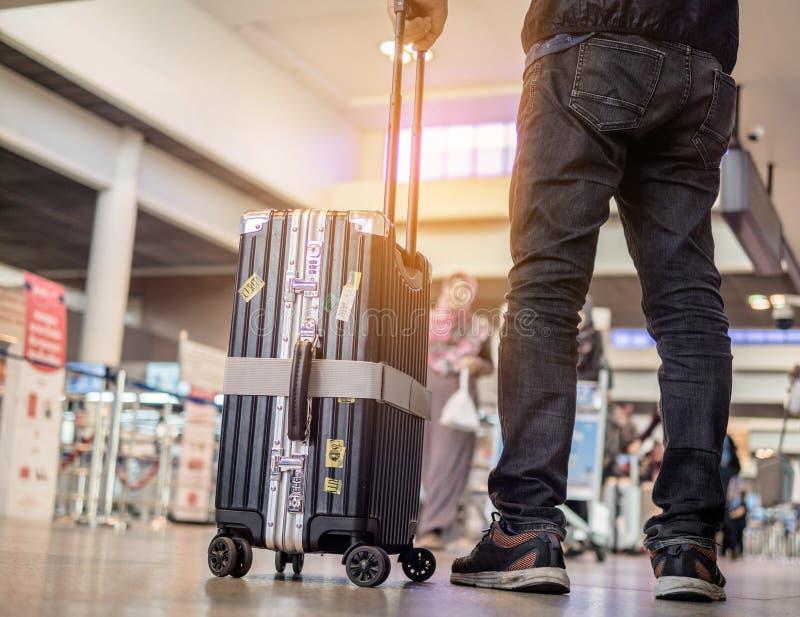 Mens die zich met bagage bij luchthaven bevinden mens die zitkamer bekijken die vliegtuigen bekijken terwijl het wachten bij het  stock foto's