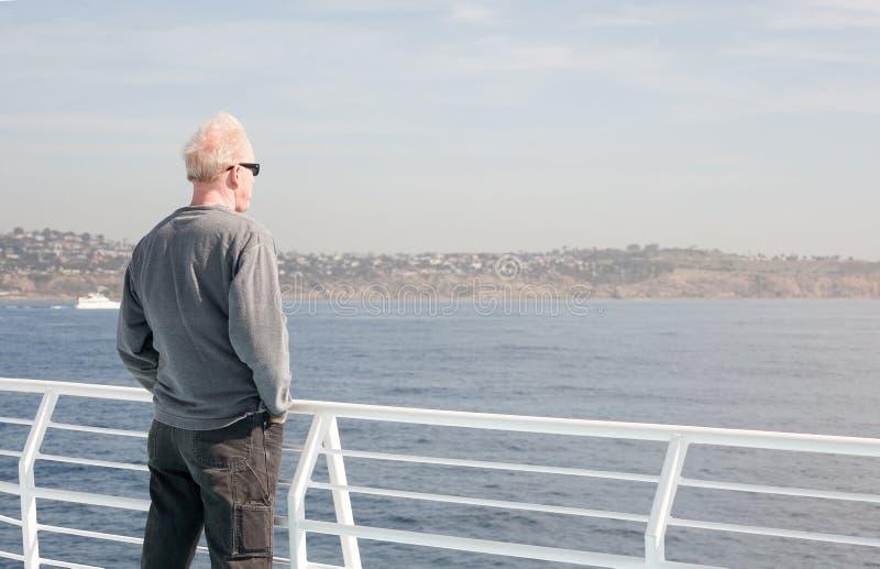 Mens die zich op boot bevinden die uit aan water kijken royalty-vrije stock afbeeldingen