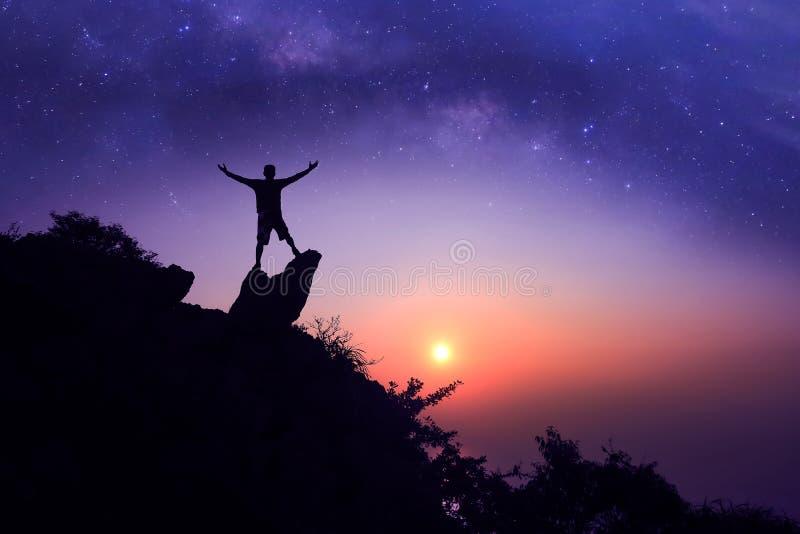 Mens die zich op de berg met miljoen sterrenmelkweg bevinden royalty-vrije stock afbeelding