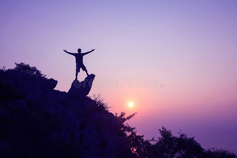 Mens die zich op de bovenkant van de berg bevinden die zonsondergang bekijken royalty-vrije stock foto
