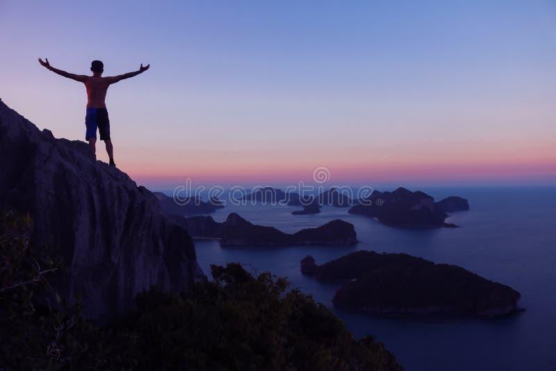 Mens die zich op de bovenkant van de berg bevindt die zonsondergang archipel bekijkt stock fotografie