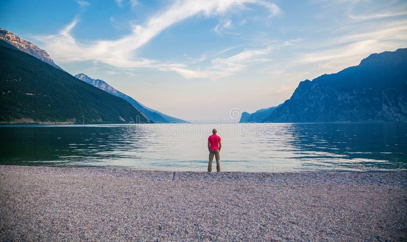 Mens die zich op de rand van Garda-meer bevinden royalty-vrije stock foto's