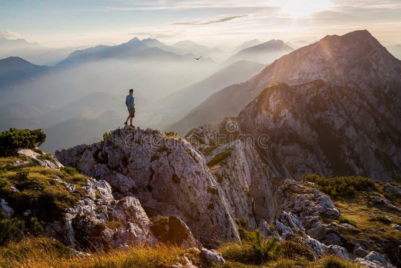 Mens die zich op een bergtop bij zonsondergang bevinden stock foto's