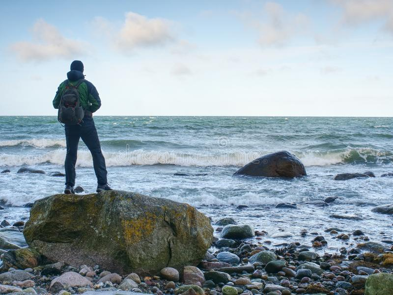Mens die zich op rots in het midden van oceaan bevinden Alleen toeristentribune stock foto's