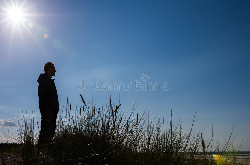 Mens die zich op zandduin bevinden en op zee silhouet kijken royalty-vrije stock foto