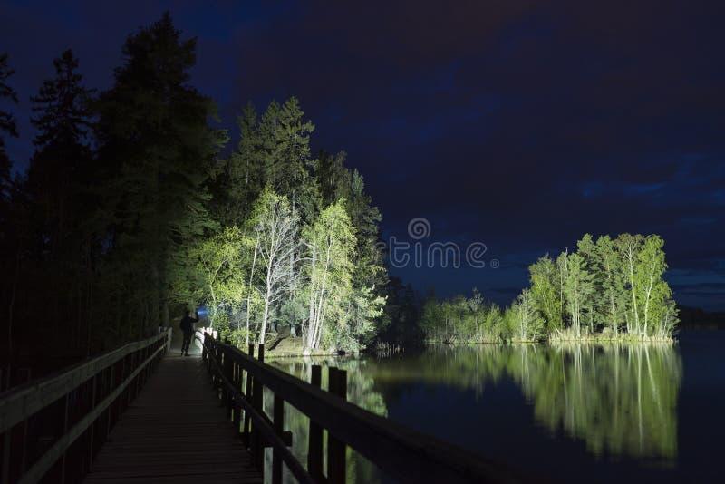 Mens die zich openlucht bij donkere nacht die met flitslicht glanzen bevinden stock foto's