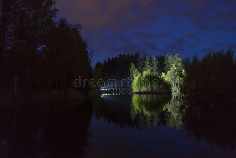 Mens die zich openlucht bij donkere nacht die met flitslicht glanzen bevinden royalty-vrije stock foto's