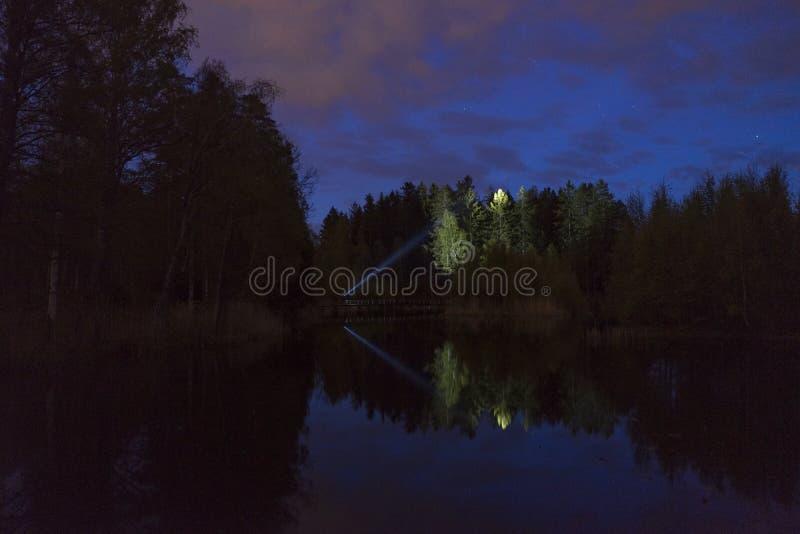 Mens die zich openlucht bij donkere nacht die met flitslicht glanzen bevinden royalty-vrije stock foto