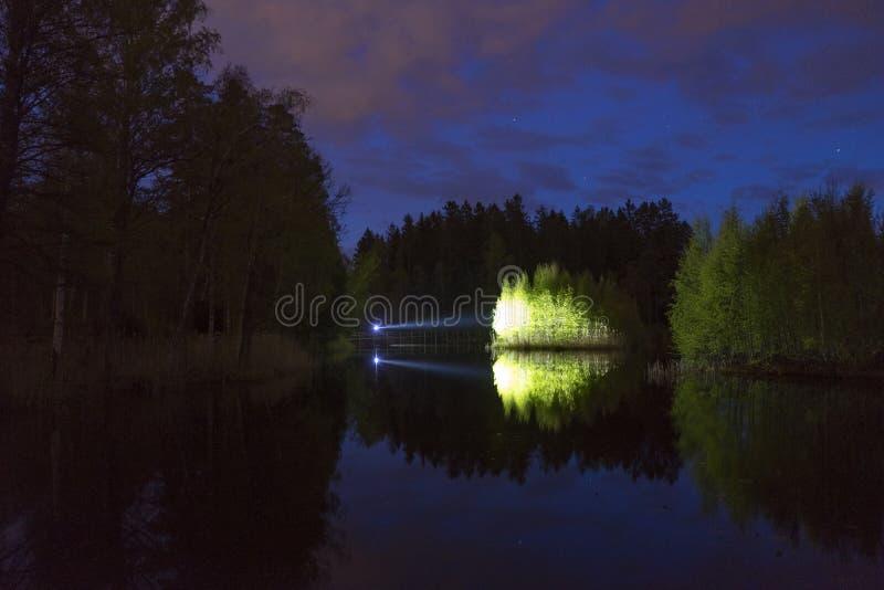 Mens die zich openlucht bij donkere nacht die met flitslicht glanzen bevinden stock foto